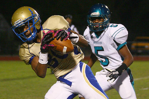 Darius Knight-Elliott of Phoebus makes this catch for a touchdown in front of Jordan Williams of Woodside during the third quarter Friday at Darling Stadium.
