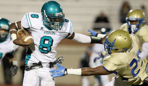 Darius Howell of Woodside stiff-arms Michael Hunt of Phoebus as he tries to get out of the backfield during the third quarter Friday at Darling Stadium.