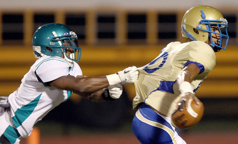 Phoebus quarterback Terrell Toliver tries to roll away from Jay'quan Lassiter of Woodside during the first quarter Friday at Darling Stadium.