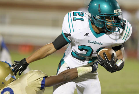 Sam Alvarez of Woodside sheds Haasan Price of Phoebus as he runs during the first quarter Friday at Darling.