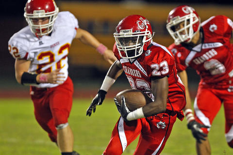 Hampton's Tyquon Wilkins, center, runs away from Gloucester's Troy Shackelford, left, during Thursday's game at Darling Stadium.