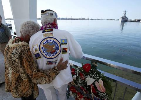Pearl Harbor survivor Dalton Walling and his fiance Joan Pohl look down at the sunken USS Arizona and the USS Missouri in the background while on board the USS Arizona Memorial during the 72nd anniversary of the attack on Pearl Harbor at the WW II Valor in the Pacific National Monument in Honolulu, Hawaii on December 7, 2013.