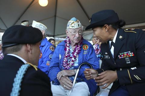 Pearl Harbor survivor Sam Clower talks with U.S. Army Sargeant Winney Clower (R) and U.S. Army Specialist Kevin Stevens during the 72nd anniversary of the attack on Pearl Harbor at the WW II Valor in the Pacific National Monument in Honolulu, Hawaii on December 7, 2013.
