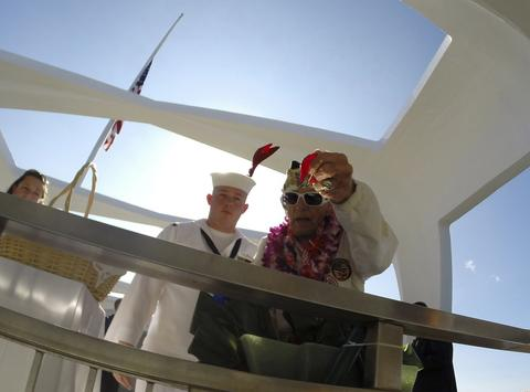 "Pearl Harbor survivor Allen Bodenlos drops rose pedals into the ""Rememberance Well"" as US Navy CTR1 Michael Temple watches while aboard the USS Arizona Memorial during the 72nd anniversary of the attack on Pearl Harbor at the WW II Valor in the Pacific National Monument in Honolulu, Hawaii on December 7, 2013."