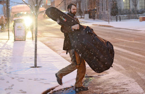 John Hartzell of Bangor carries his wife's string bass across 6th Street heading towards the Allentown Transportation Center Parking Deck after the Allentown Band's Annual Holiday/Pearl Harbor Remembrance Concert at Miller Symphony Hall in Allentown Sunday evening. His wife, Kara Hartzell of Bangor plays string bass in the Allentown Band. The crowds leaving were faced with a fresh coating of snow covering the cars, roads, and sidewalks.