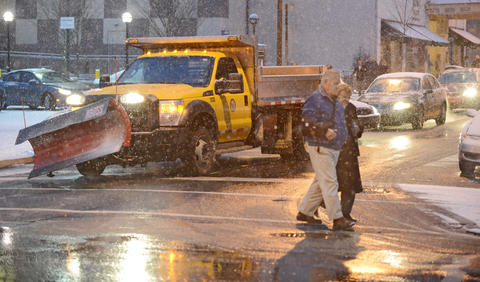 Bruce and Louise Stettler of Schnecksville walk across 6th Street heading towards the Allentown Transportation Center Parking Deck after the Allentown Band's Annual Holiday/Pearl Harbor Remembrance Concert at Miller Symphony Hall in Allentown Sunday evening. The crowds leaving were faced with a fresh coating of snow covering the cars, roads, and sidewalks.