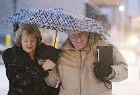 "Phyllis and Kurt McDowell use an umbrella to shield them from the snow as they carefully walk down a snowy sidewalk on 6th Street in Allentown after the Allentown Band's Annual Holiday/Pearl Harbor Remembrance Concert at Miller Symphony Hall in Allentown Sunday evening. Kurt performed in the concert with Summer Harmony and thought the concert was successful saying, ""it was great, it was a lot of fun, it always is."" The crowds leaving were faced with a fresh coating of snow covering the cars, roads, and sidewalks."