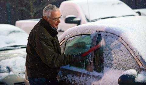 Joseph Soska of Bethlehem uses an ice scraper to clean off his car after the Allentown Band's Annual Holiday/Pearl Harbor Remembrance Concert at Miller Symphony Hall in Allentown Sunday evening. The crowds leaving were faced with a fresh coating of snow covering the cars, roads, and sidewalks.
