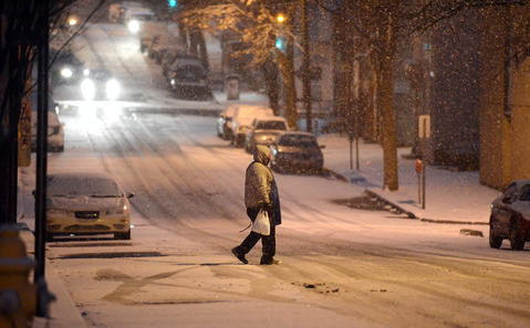 A man carefully walks across a snow covered 5th Street in Allentown Sunday evening.