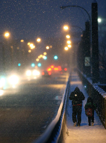 Pedestrians cross the snow covered 8th Street bridge in Allentown Sunday December 8, 2013.