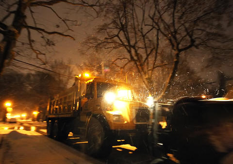 A snow plow spreads salt on the road as it makes its way down Allen Street in Allentown Sunday December 8, 2013.