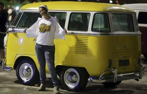A woman poses for a photograph in front of a customized Volkswagen Kombi minibus during a Kombi fan club meeting in Sao Paulo September 24, 2013. Volkswagen Brazil, the last plant to produce the Kombi, will cease production of the iconic vehicle on December 20 after 56 years of production. Higher manufacturing costs and increase in production time due to new auto regulations, which will require anti-lock brake systems and air bags in all cars produced in Brazil from 2014, contributed to its decision to stop the production of the Kombi, according to the company.