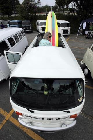 A man arranges his surfboard inside his Volkswagen Kombi minibus during a Kombi fan club meeting in Sao Bernardo do Campo December 8, 2013. Volkswagen Brazil, the last plant to produce the Kombi, will cease production of the iconic vehicle on December 20 after 56 years of production. Higher manufacturing costs and increase in production time due to new auto regulations, which will require anti-lock brake systems and air bags in all cars produced in Brazil from 2014, contributed to its decision to stop the production of the Kombi, according to the company.
