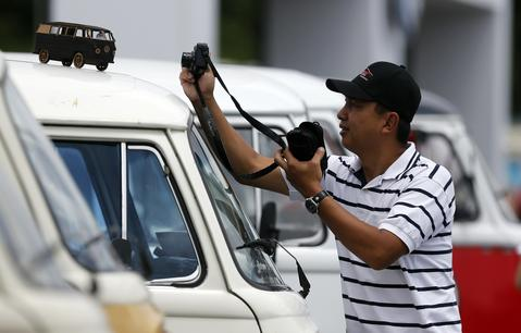 A man takes a photograph of a miniature Kombi car during a Kombi fan club meeting in Sao Bernardo do Campo December 8, 2013. Volkswagen Brazil, the last plant to produce the Kombi, will cease production of the iconic vehicle on December 20 after 56 years of production. Higher manufacturing costs and increase in production time due to new auto regulations, which will require anti-lock brake systems and air bags in all cars produced in Brazil from 2014, contributed to its decision to stop the production of the Kombi, according to the company.