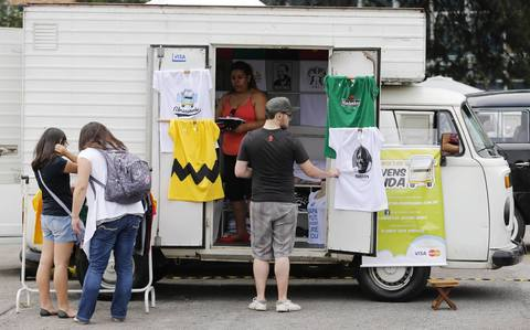 People look at t-shirts on sale at a customized Volkswagen Kombi minibus during a Kombi fan club meeting in Sao Bernardo do Campo December 8, 2013. Volkswagen Brazil, the last plant to produce the Kombi, will cease production of the iconic vehicle on December 20 after 56 years of production. Higher manufacturing costs and increase in production time due to new auto regulations, which will require anti-lock brake systems and air bags in all cars produced in Brazil from 2014, contributed to its decision to stop the production of the Kombi, according to the company.