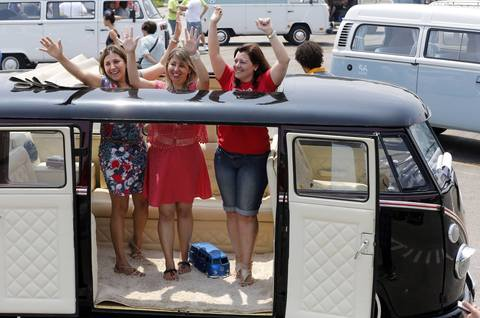 Visitors pose for a photograph inside a Volkswagen Kombi minibus during a Kombi fan club meeting in Sao Bernardo do Campo December 8, 2013. Volkswagen Brazil, the last plant to produce the Kombi, will cease production of the iconic vehicle on December 20 after 56 years of production. Higher manufacturing costs and increase in production time due to new auto regulations, which will require anti-lock brake systems and air bags in all cars produced in Brazil from 2014, contributed to its decision to stop the production of the Kombi, according to the company.