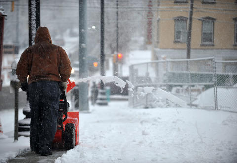 A man uses a snow blower to clear the sidewalks on 7th Street in Allentown Tuesday morning.