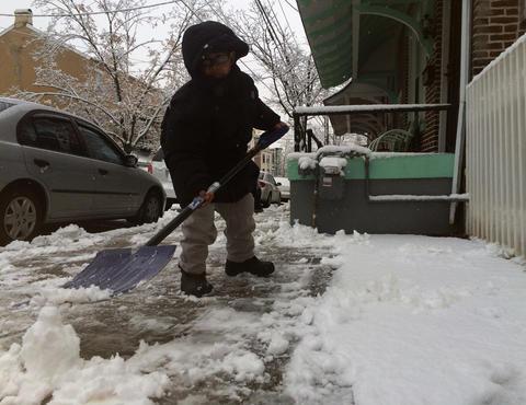 Jayden Ortiz, 8, helps his dad shovel snow Tuesday morning on Turner Street in Allentown.