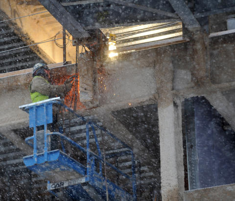 A worker on the construction site of the future hockey arena in Allentown welds in snowy conditions on Tuesday morning.