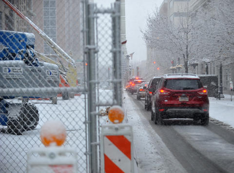 Traffic moves slowly on Hamilton Street in Allentown Tuesday morning as snow continues to blanket the roadways.