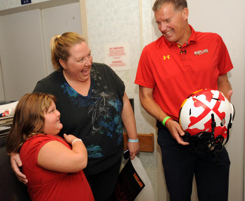 Terps coach Randy Edsall shares a laugh with patient Trinity Merritt, 7, and her mother, Carrie Merritt.