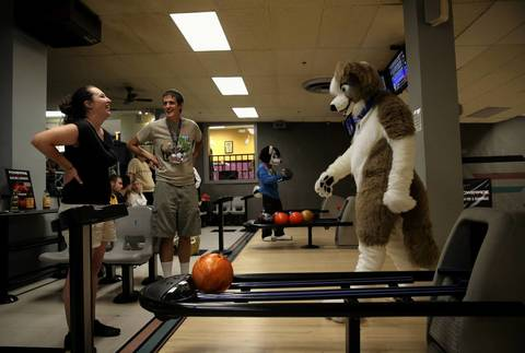 Mike Nicely, dressed as Woofie McBarkums, walks back to his seat while bowling with his girlfriend, Maggie Solum.