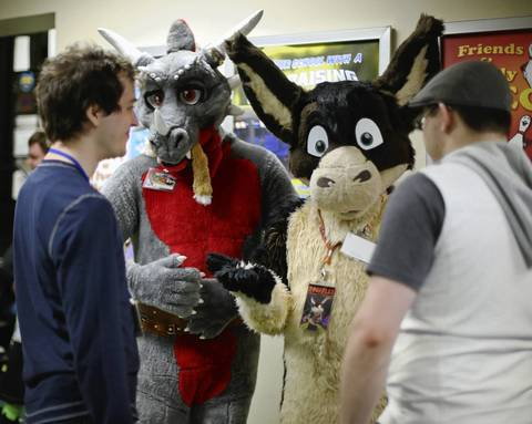 Two fur-suited men talk with friends.