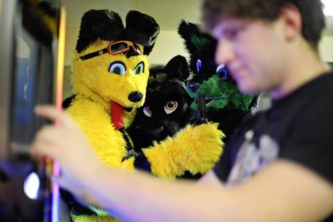 A trio of fur-suited friends watch Avi Kritzman, 19, of Buffalo Grove, pick songs on a jukebox.