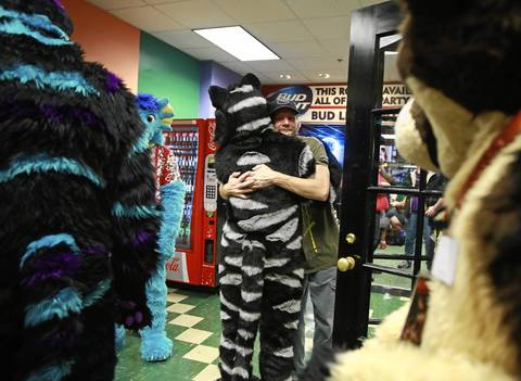 Jeff Keith, 38, of Round Lake hugs a fur-suited friend.