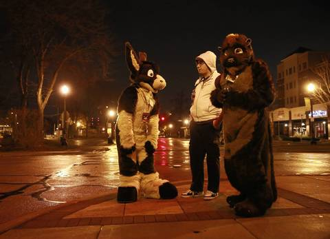 Two furries stand on the street outside the bowling alley.