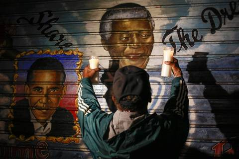 A man holds candles in front of a mural of former South African President Nelson Mandela (center) and U.S. President Barack Obama in New York. Mandela died peacefully at his Johannesburg home after a prolonged lung infection, President Jacob Zuma said.