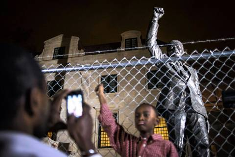 Dijon Anderson of Bowie, Maryland, photographs his son Keaton, 10, in front of a statue of Nelson Mandela at the South African embassy in Washington, DC.
