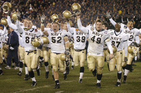 Navy players run towards their classmates as they celebrate four straight wins over Army in 2005.