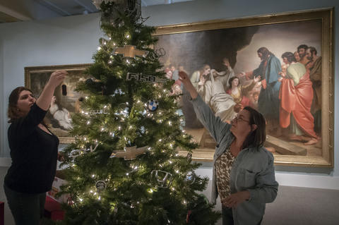 "2013.12.01 - Hartford, CT - ""Paula's been wanting to do this for years,"" says Jaime Gilbride (L) of her friend Paula Thompson (right). as the two decorate a tree inside the Wadsworth Atheneum's Austin Gallery in front of a 1780 painting by Benjamin West named ""The Raising of Lazarus."" For the past year, Thompson, who works at Olender's Body Shop, has been collecting emblems from cars brought in for repair and now, for her first time, is providing a tree for the Wadsworth Atheneum's Festival of Trees & Traditions. Running through December 14, this is the 40th year of the festival with approximately 155 Christmas items displayed across six Atheneum galleries."