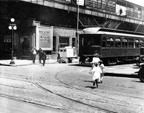 The Englewood elevated train station looms overhead as children run after a streetcar at 63d and Halsted Streets, ca. 1920.