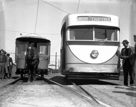 The new streetcar, on the right, and the old fashioned, horse-drawn street car on the left, ca. April 23, 1934.