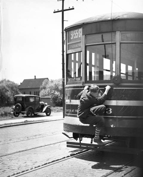 A boy hops a ride on a streetcar on 51st Street near Western Avenue. The photo was taken from the window of a passing auto on June 6, 1937.