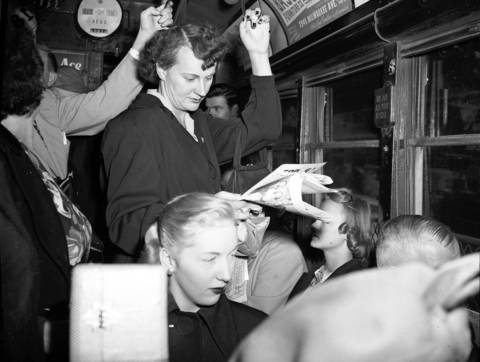 """This woman """"strap hanger"""" complained about not being able to read her paper because there were no lights on the Milwaukee Avenue Street car on Sept. 8, 1949."""