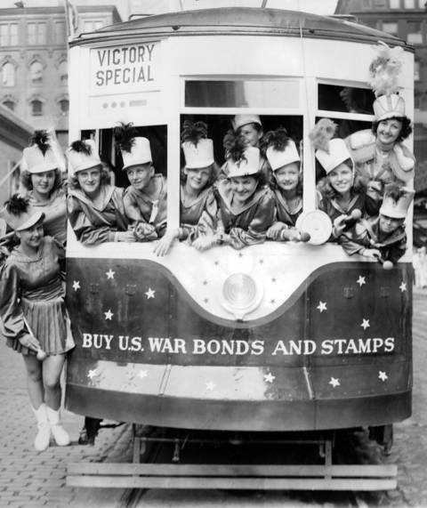 Majorettes help sell war bonds and stamps in a streetcar painted red, white, and blue during World War II. The car went into regular service on the Broadway Avenue line in July 1942.