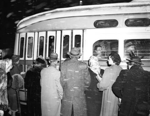 People wait in the cold and snow to board the Clark and Howard streetcar at Clark and Randolph Streets, going north at 4:58pm on Nov. 30, 1949.