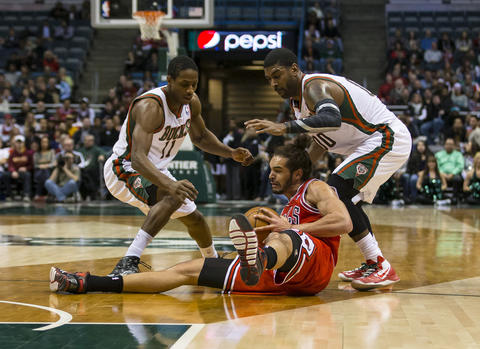Joakim Noah holds onto the ball between the Bucks' Brandon Knight and O.J. Mayo during the first quarter.