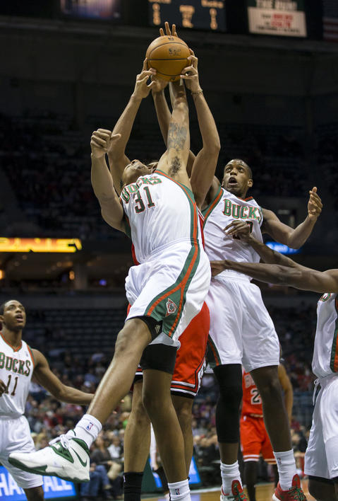 The Bucks' John Henson reaches for a rebound during the first quarter.