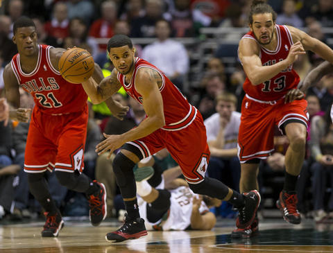 D.J. Augustin heads up court with the ball in front of Jimmy Butler (21) and Joakim Noah.