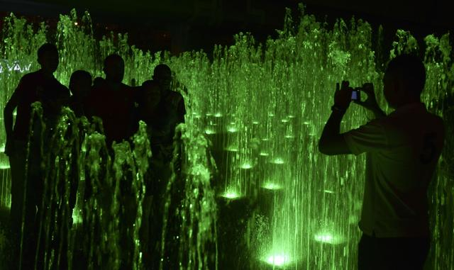 People attend the Christmas lights illumination along the Medellin river on December 9, 2013 in Medellin, Antioquia department, Colombia.