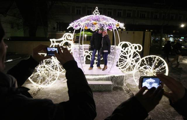 People take pictures of a couple posing with a light decoration during the annual illumination of Christmas lights at Krakowskie Przedmiescie street, part of the historical Trakt Krolewski (The Royal Route), in Warsaw December 7, 2013.