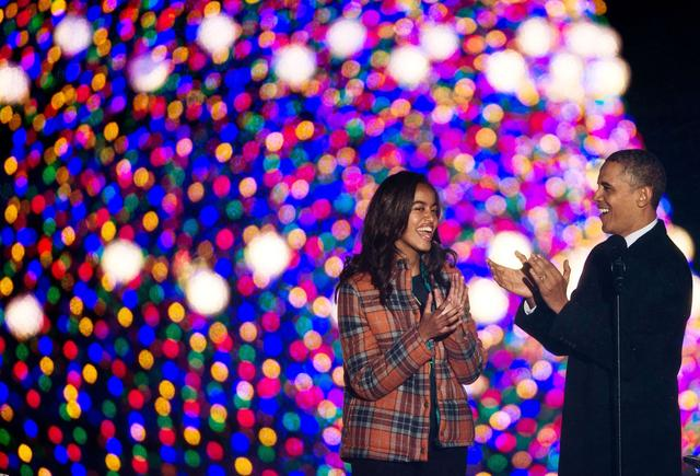 President Barack Obama (right) and daughter Malia applaud after lighting the National Christmas Tree on the Ellipse near the White House in Washington on Dec. 6, 2013.