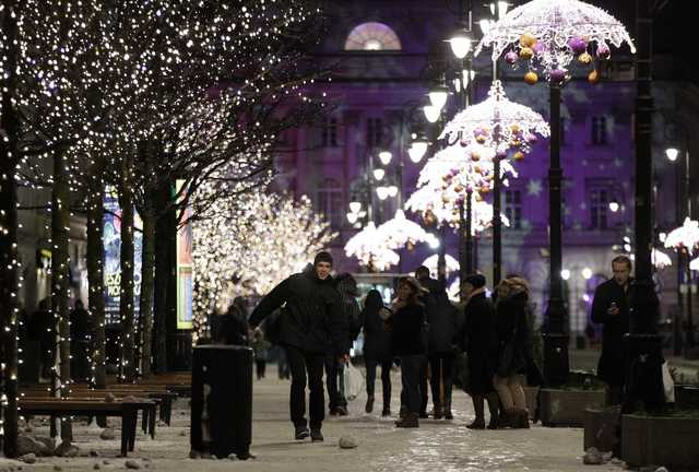 People walk under light decorations during the annual illumination of Christmas lights at Krakowskie Przedmiescie street, part of the historical Trakt Krolewski (The Royal Route), in Warsaw December 7, 2013.