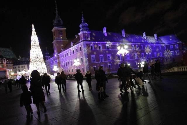 People walk near a Christmas tree during the annual illumination of Christmas lights in front of the Royal Castle in Warsaw December 7, 2013.