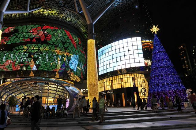 Pedestrians walk past as a shopping mall is illuminated with colourful lights for the festive Christmas season in Singapore's Orchard road shopping district on December 9, 2013. As Christmas approaches, Singapore's bustling Orchard Road is decorated with lights and advertising displays to lure shoppers.