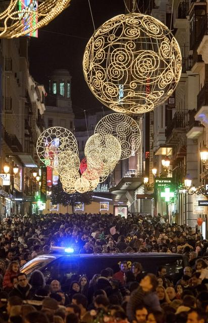 Christmas lights illuminate the Preciados street as police closes it due to the crowd visiting the centre of Madrid on December 7, 2013.